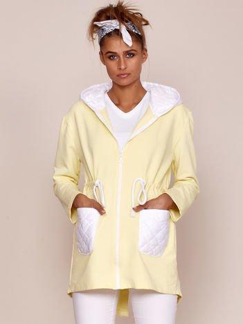Żółta bluza z białymi pikowanymi kieszeniami i kapturem