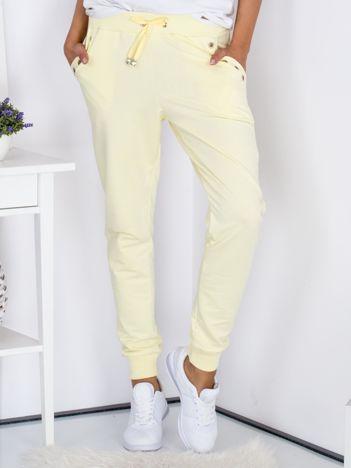 Żółte spodnie dresowe z ażurowym wykończeniem kieszeni
