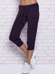 Ciemnofioletowe spodnie capri z dżetami przy kieszeniach