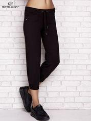 Czarne spodnie dresowe capri z aplikacją na kieszeniach