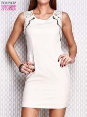 Kremowa dopasowana sukienka z koronkowymi wstawkami