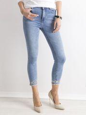 Niebieskie jeansy z aplikacją na nogawkach