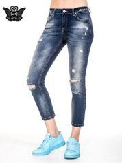 Niebieskie spodnie girlfriend jeans z rozjaśnianą nogawką i dziurami