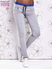Szare spodnie z przeszyciami i niebieską gumką w pasie