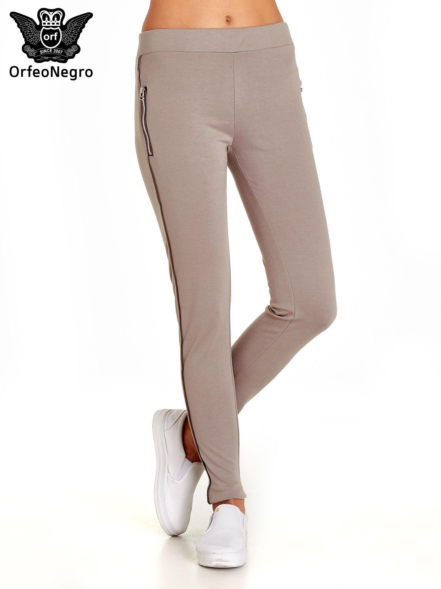 Beżowe spodnie materiałowe tregginsy ze skórzanym lampasem i zamkami                                  zdj.                                  1