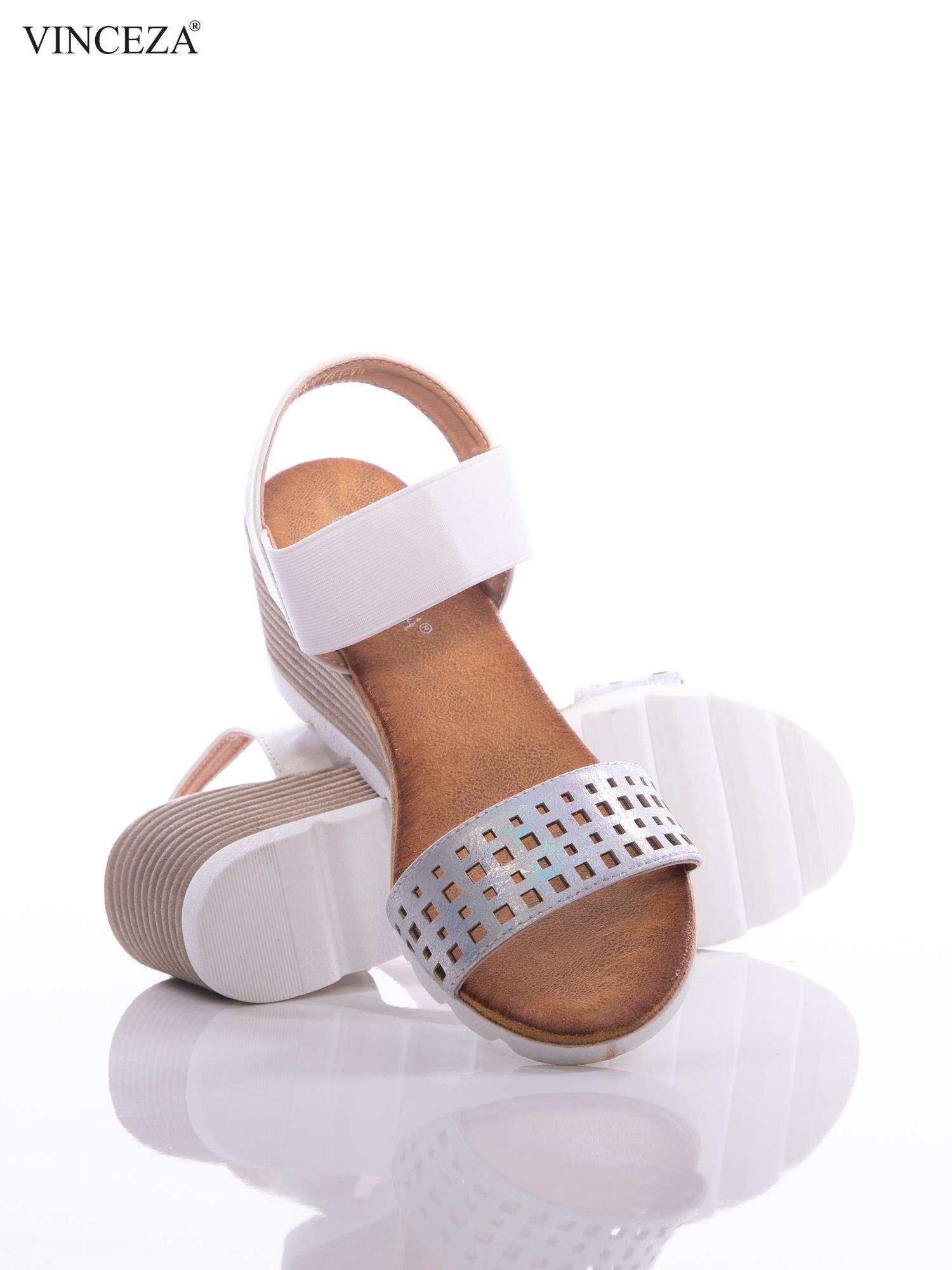 Białe sandały Vinceza na koturnach z ażurowym paskiem na przodzie i holograficzną poświatą