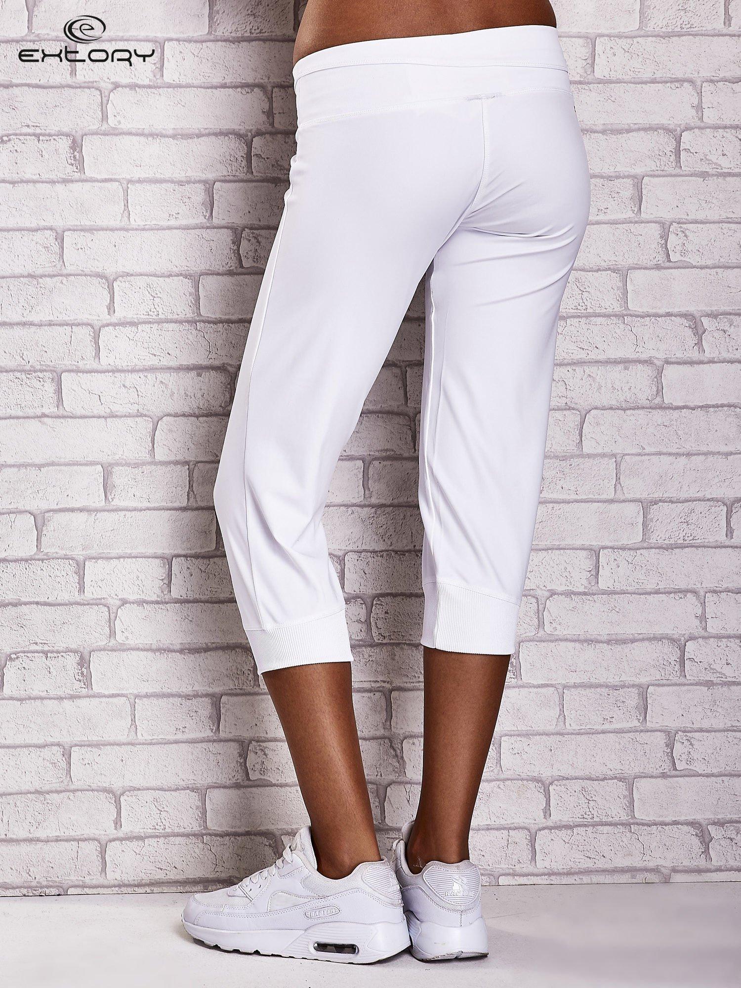 Białe śliskie spodnie capri z dżetami i troczkami                                  zdj.                                  3