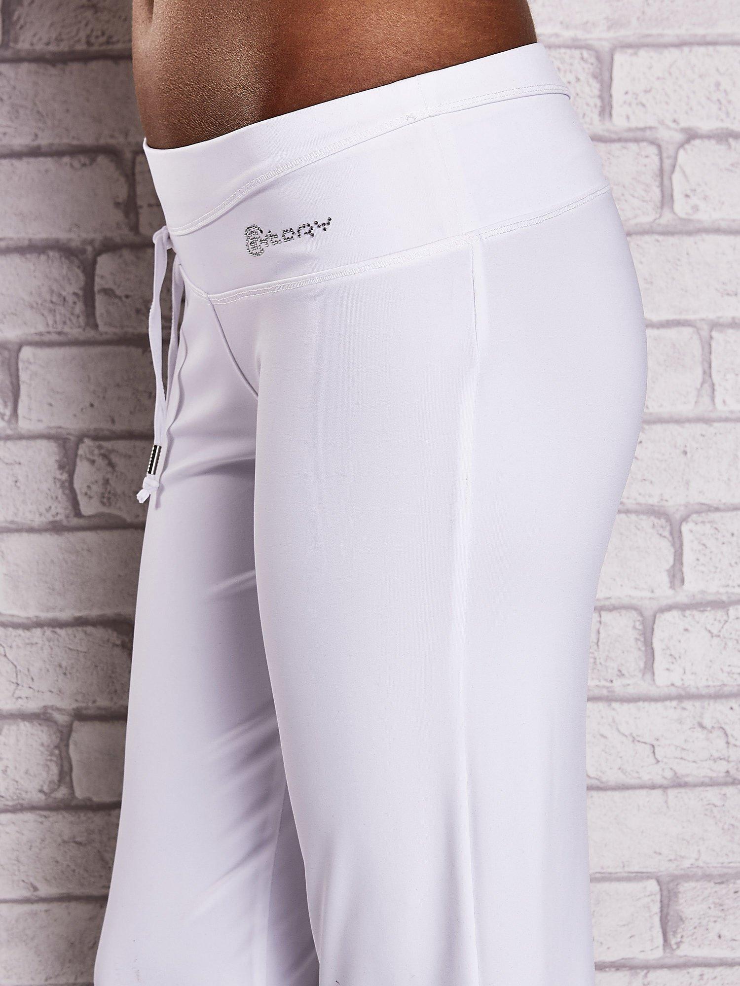 Białe śliskie spodnie capri z dżetami i troczkami                                  zdj.                                  6
