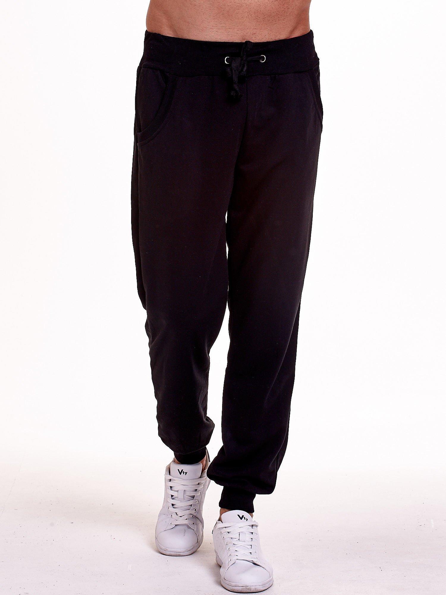 Czarne dresowe spodnie męskie z trokami w pasie i kieszeniami                                  zdj.                                  1