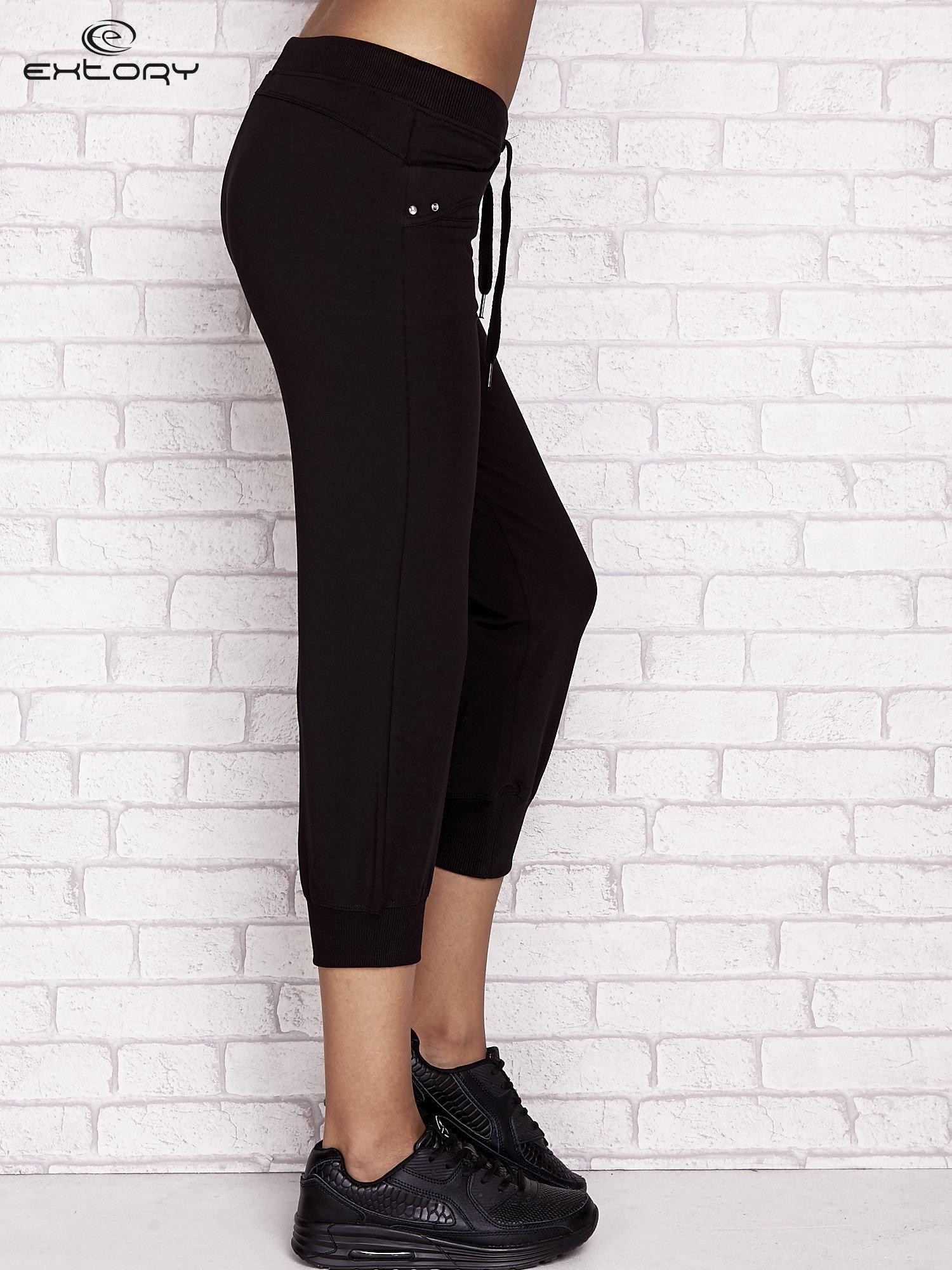 Czarne spodnie dresowe capri z aplikacją na kieszeniach                                  zdj.                                  3