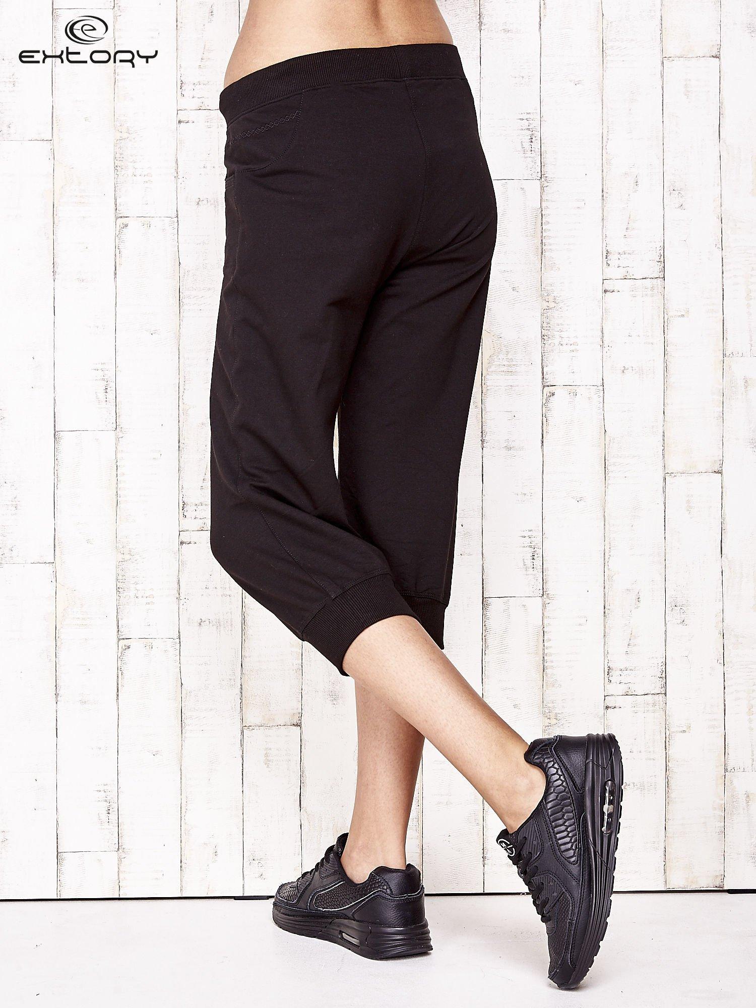 Czarne spodnie dresowe capri ze ściągaczami na dole