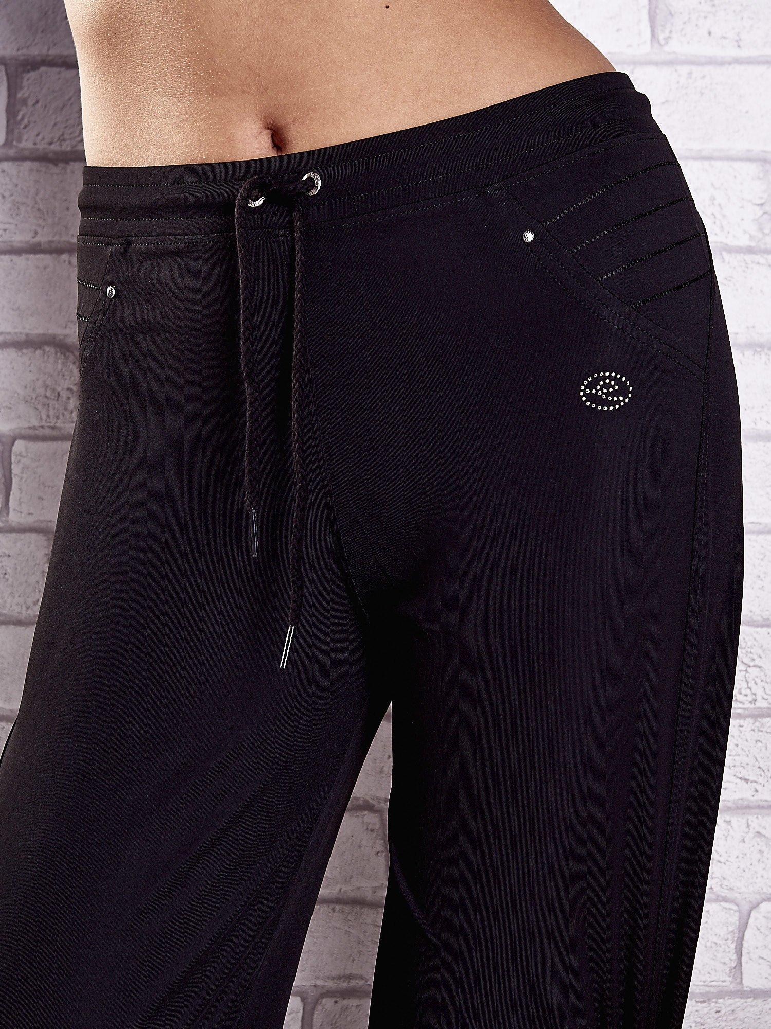 Czarne spodnie dresowe z haftowanymi wstawkami PLUS SIZE                                  zdj.                                  4
