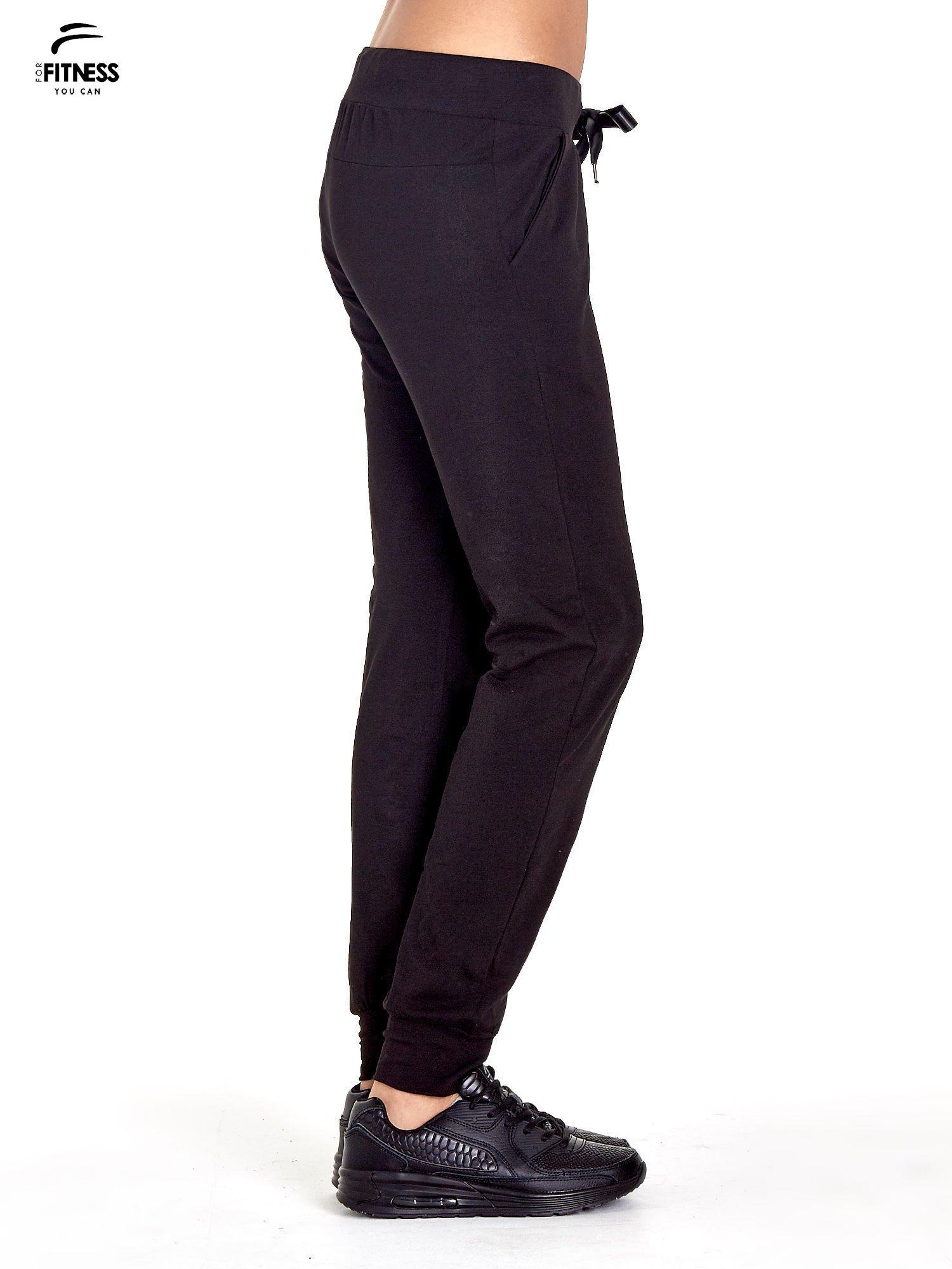 ... 4afc66f871b1 Czarne spodnie dresowe z nogawką ze ściągaczem - Spodnie  Dresowe . d7212b434ea