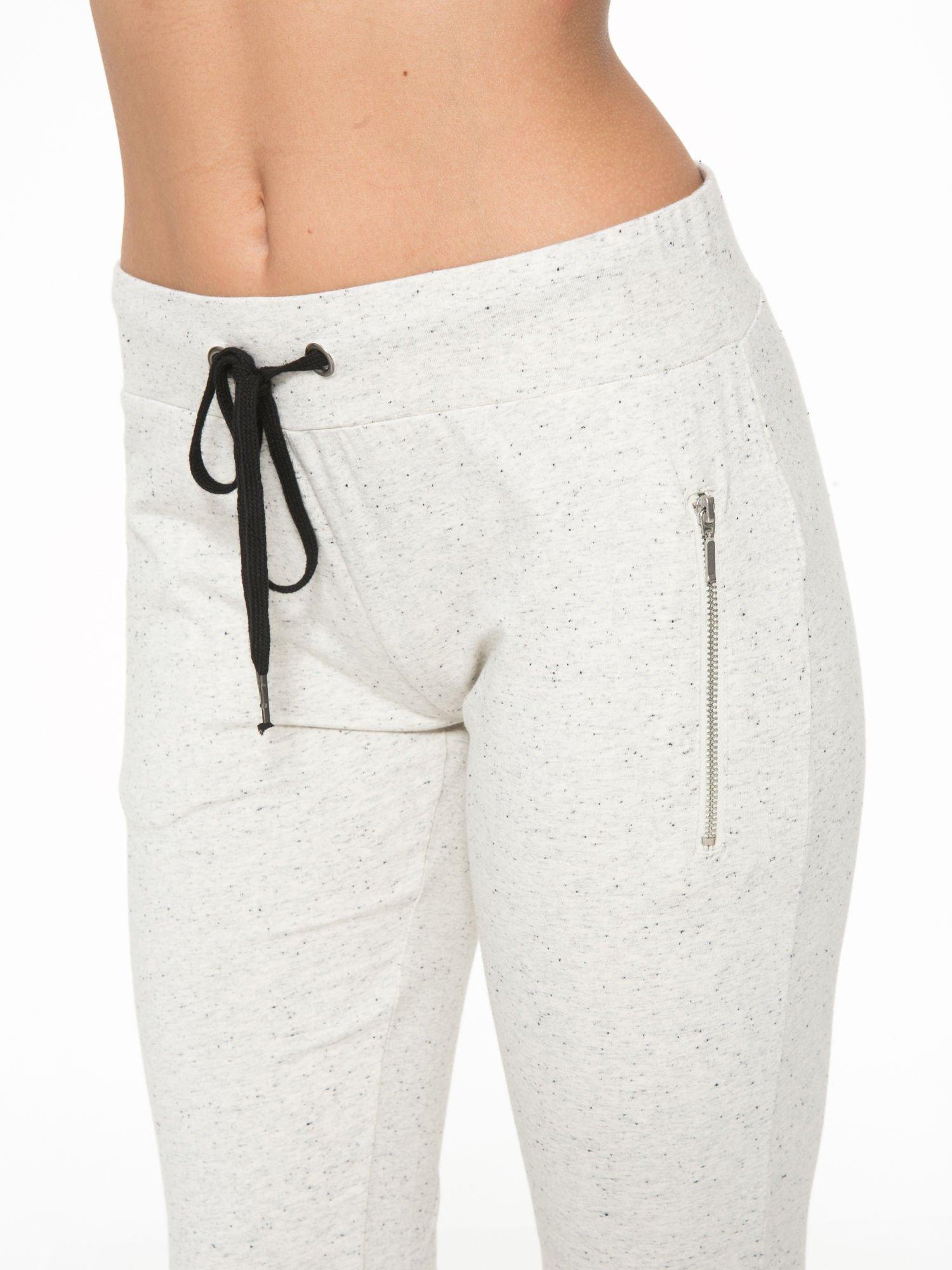 Ecru melanżowe spodnie dresowe z kieszeniami na zamek                                  zdj.                                  6