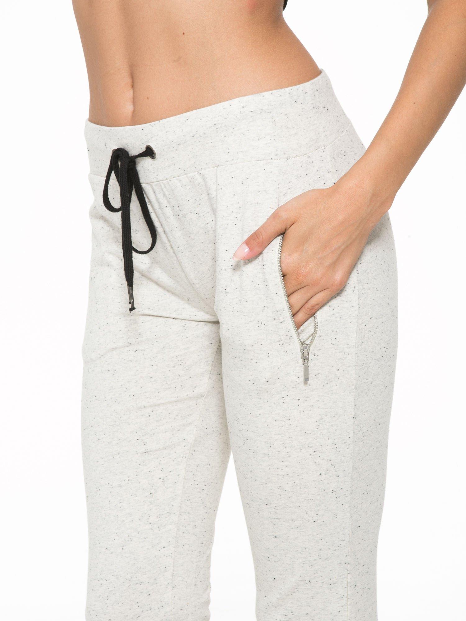Ecru melanżowe spodnie dresowe z kieszeniami na zamek                                  zdj.                                  7