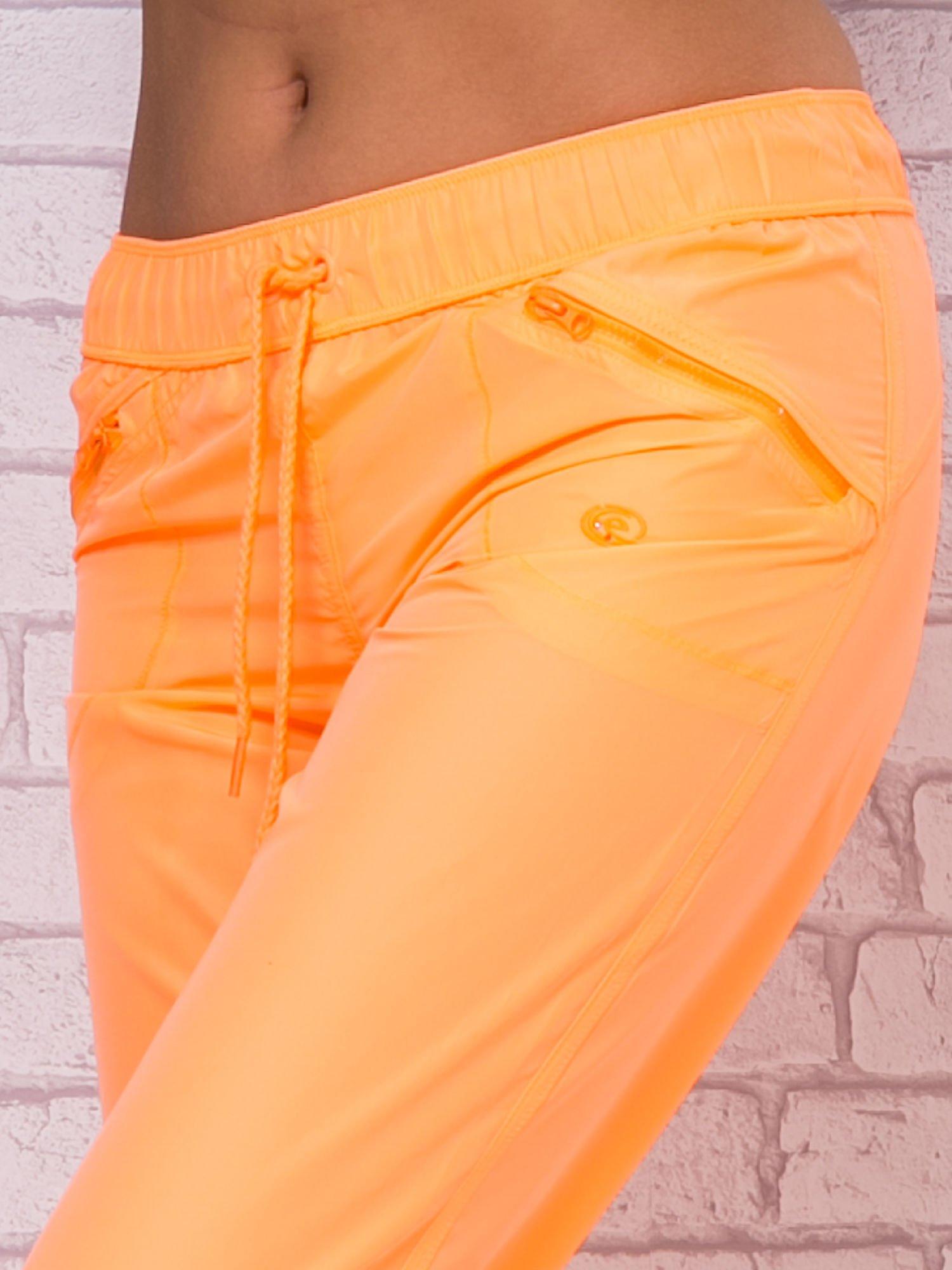Fluopomarańczowe spodnie sportowe capri z wiązaniem                                  zdj.                                  4
