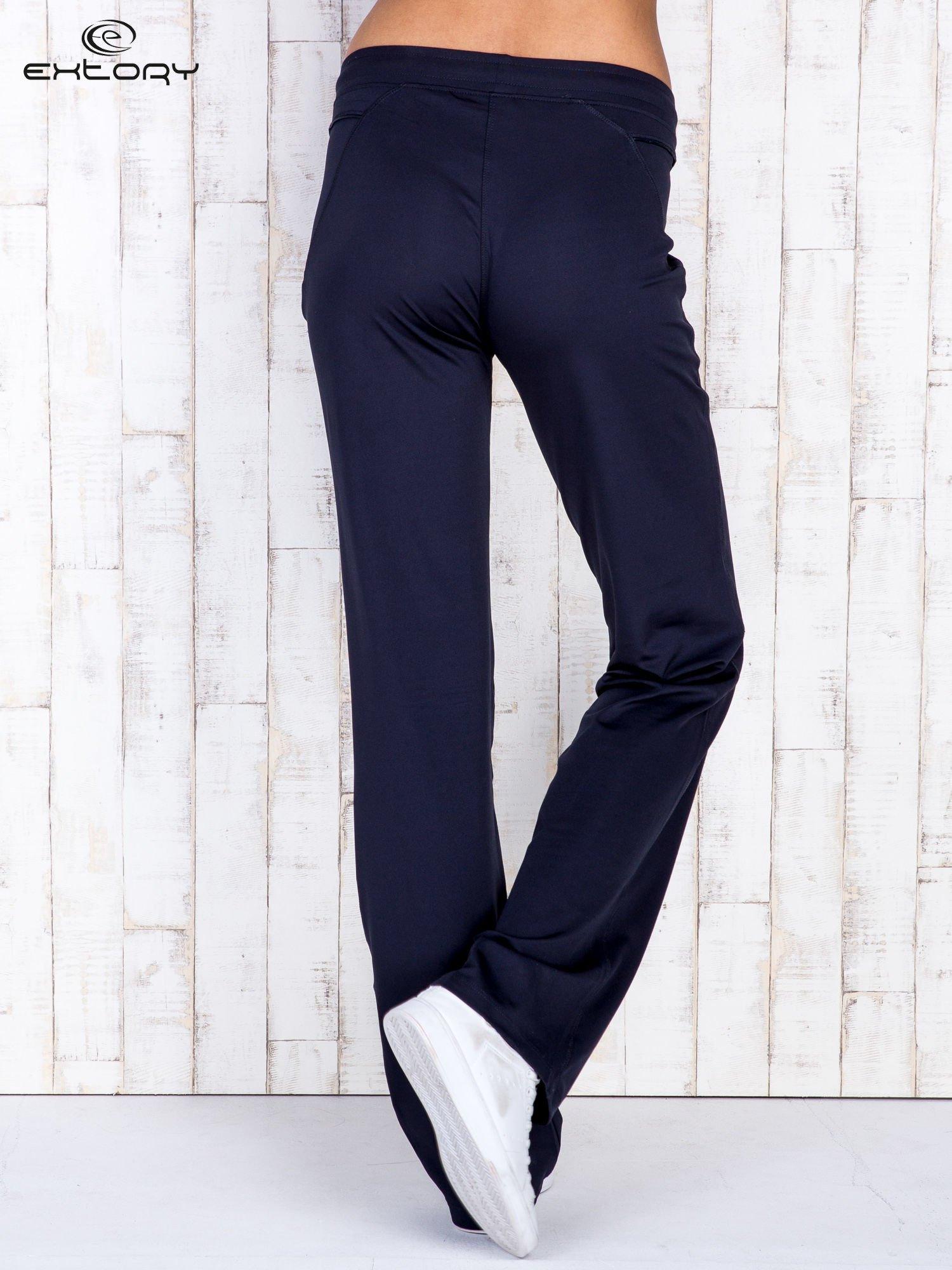 Granatowe spodnie dresowe z kieszonką i haftem PLUS SIZE                                  zdj.                                  2