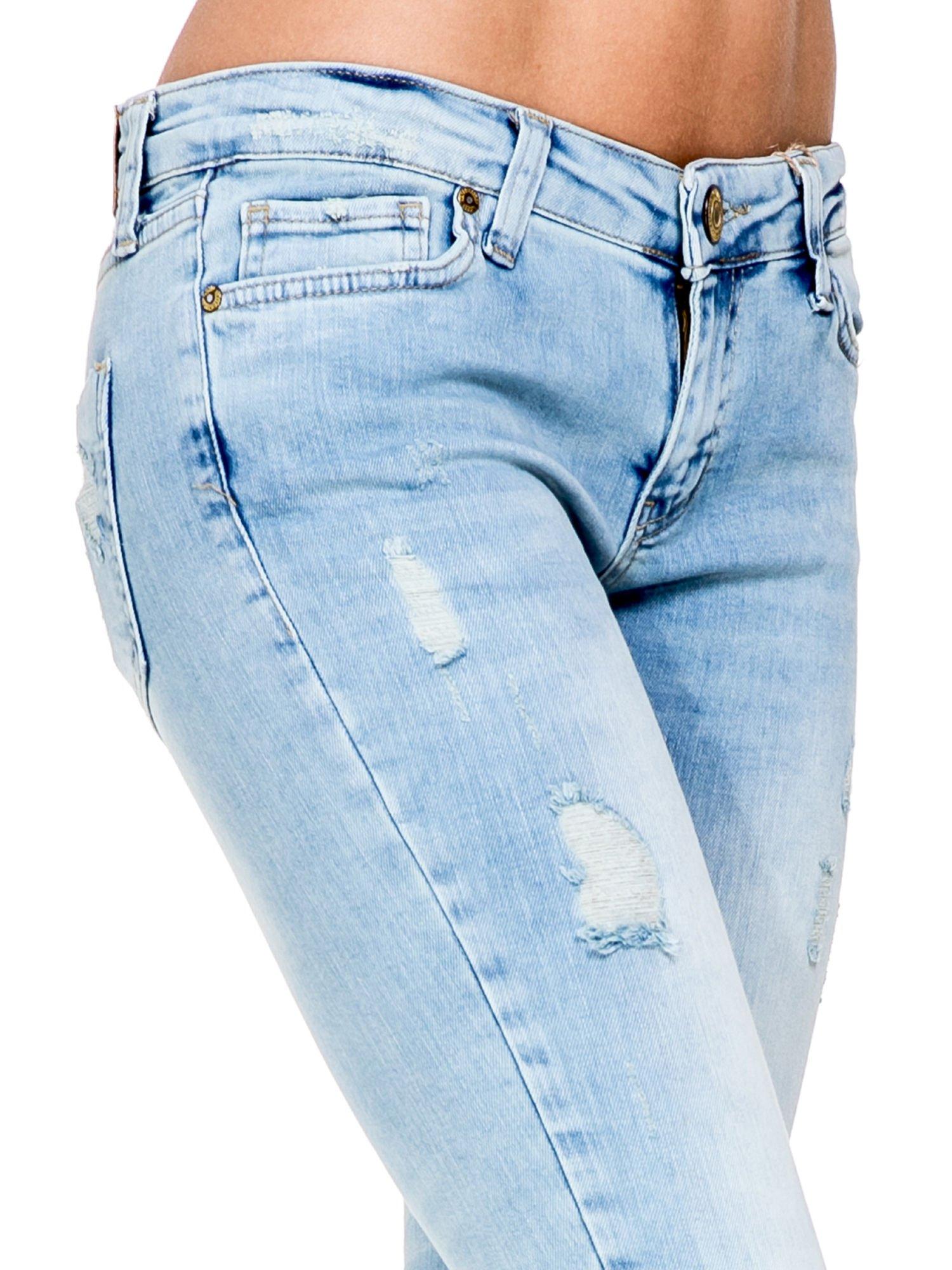 Jasnoniebieskie spodnie skinny jeans z rozdarciami na kolanie                                  zdj.                                  6