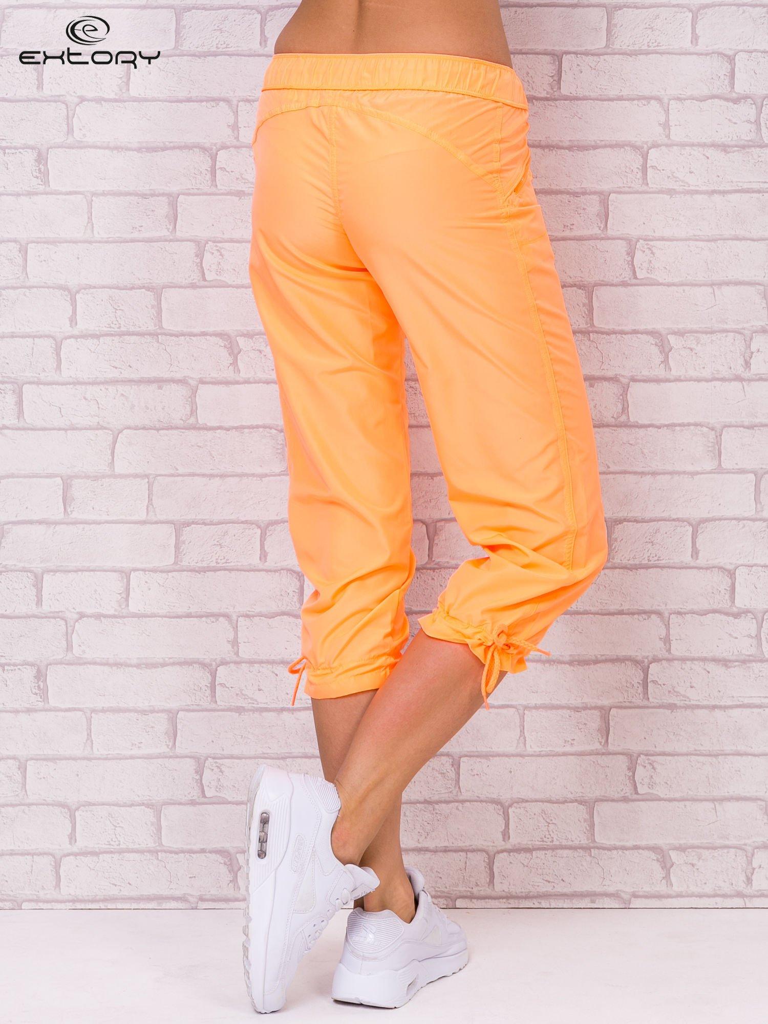 Jasnopomarańczowe spodnie sportowe capri z wiązaniem                                  zdj.                                  1