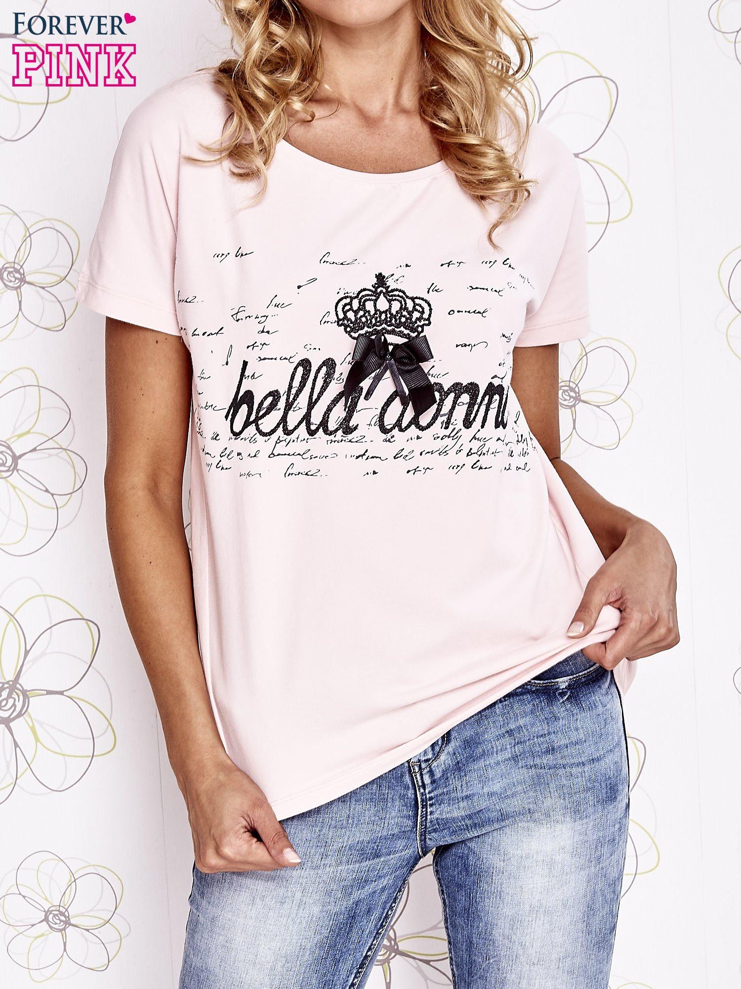 Jasnoróżowy t-shirt z ozdobnym napisem i kokardą                                  zdj.                                  1