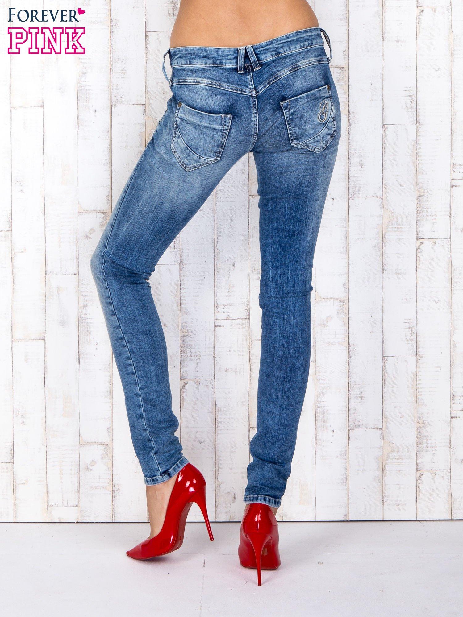 Niebieskie jeansowe spodnie rurki z przetarciami i haftami                                  zdj.                                  3