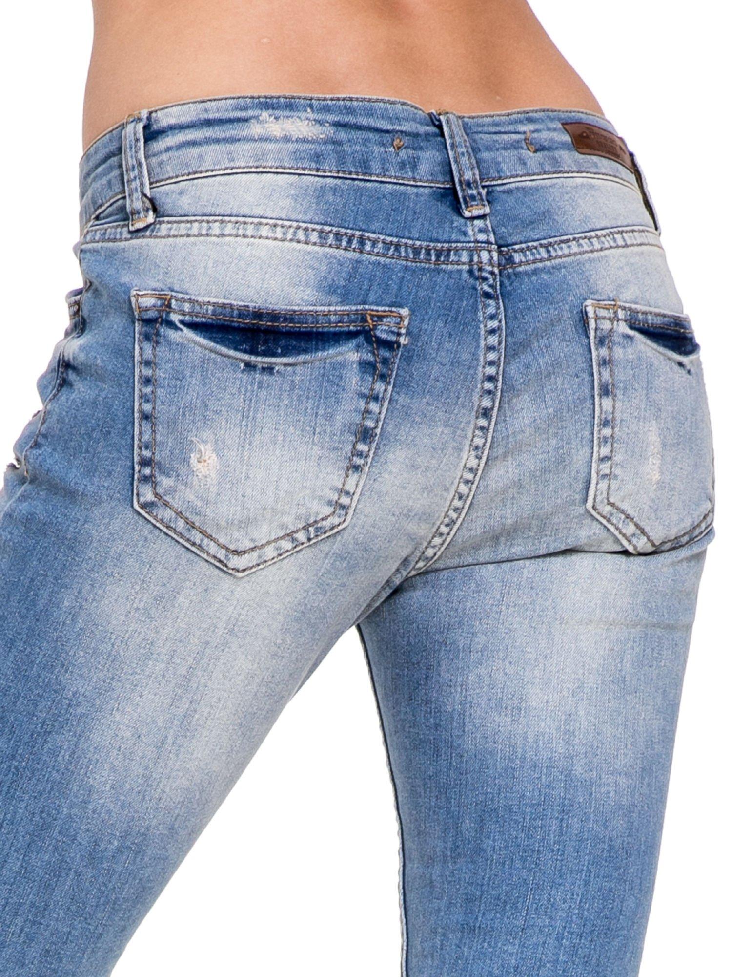 Niebieskie spodnie jeansowe do połowy łydki z licznymi przetarciami                                  zdj.                                  8