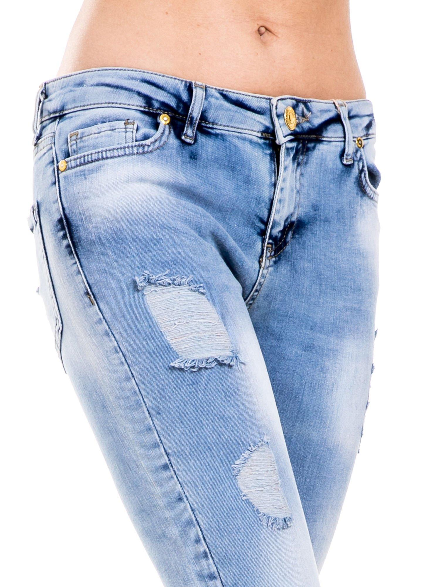 Niebieskie spodnie jeansowe z dziurami i rozdarciami                                  zdj.                                  7