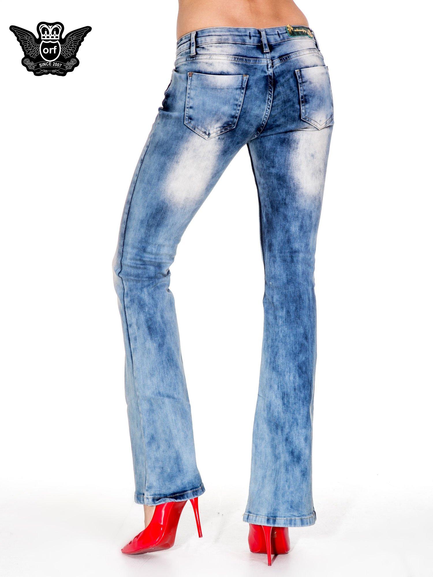 Niebieskie spodnie jeasnowe dzwony z przetarciami i rozjaśnianą nogawką                                  zdj.                                  2