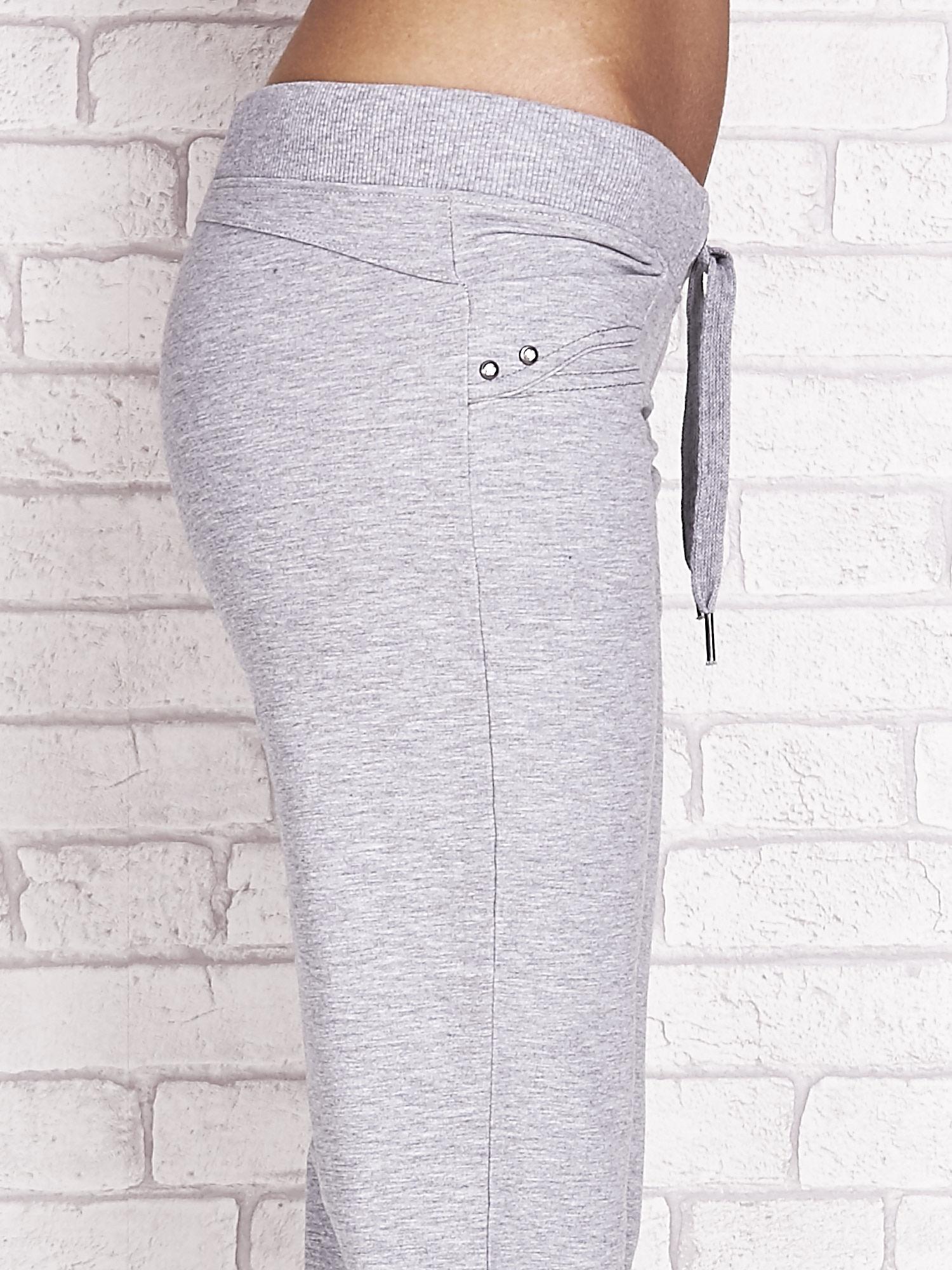 Szare spodnie dresowe capri z dżetami na kieszeniach                                  zdj.                                  5
