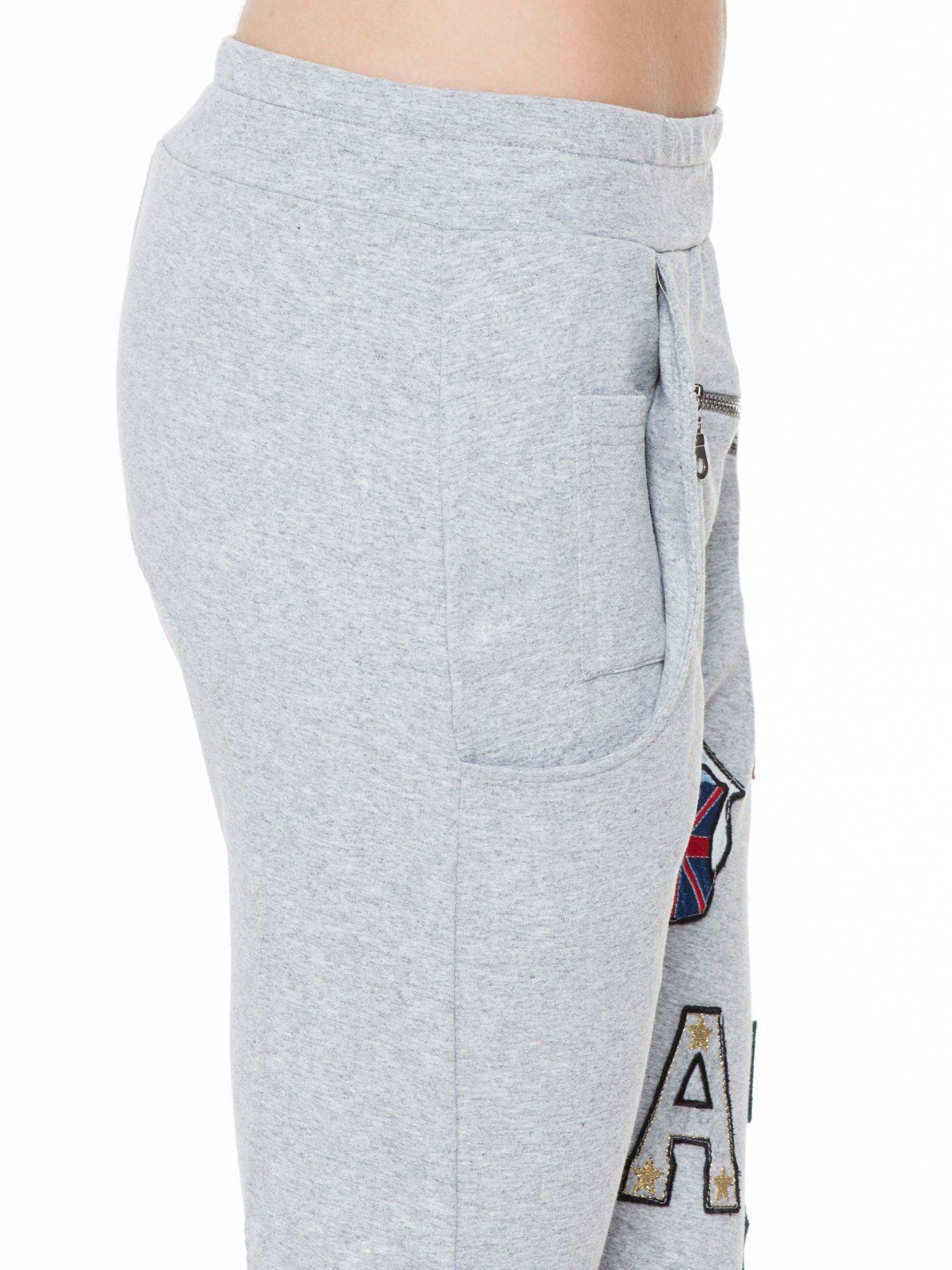 Szare spodnie dresowe typu baggy z naszywkami                                  zdj.                                  6