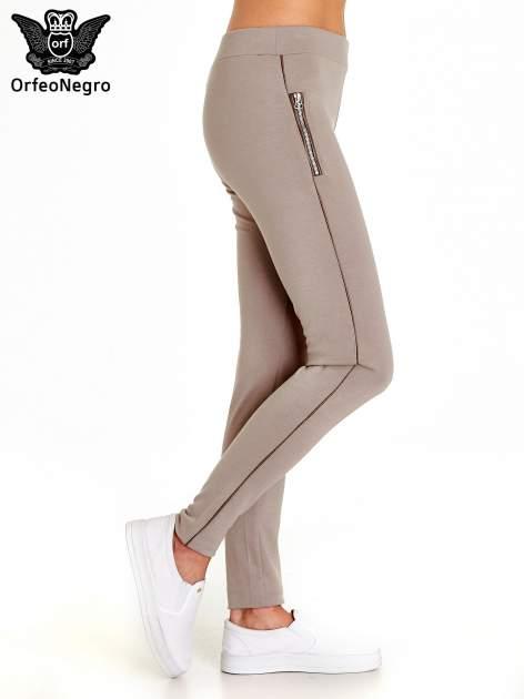 Beżowe spodnie materiałowe tregginsy ze skórzanym lampasem i zamkami                              zdj.                              3