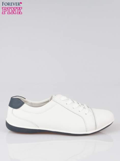 Białe buty sportowe na granatowej podeszwie