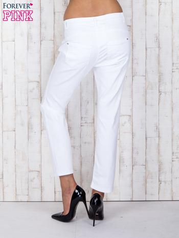 Białe jeansowe spodnie z przetarciami i guzikami                                  zdj.                                  2