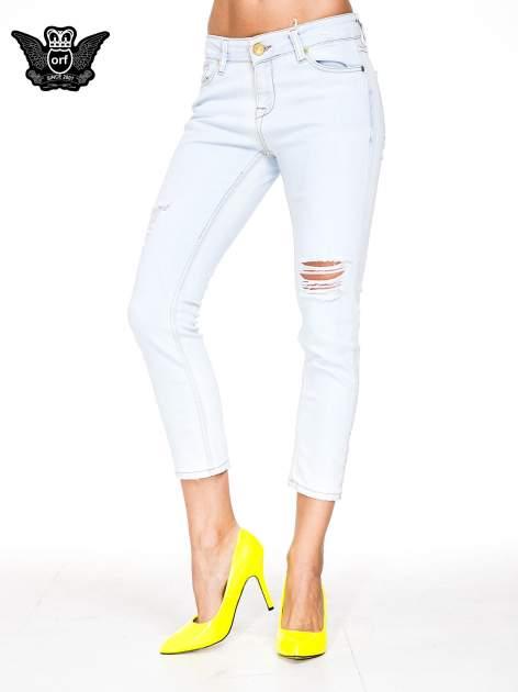 Błękitne spodnie skinny jeans z rozdarciem na udzie