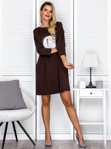 Brązowa sukienka damska oversize z perełkami i okrągłą naszywką                              zdj.                              4