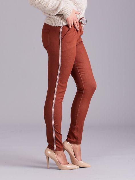 Brązowe spodnie z troczkami i lampasami                              zdj.                              2