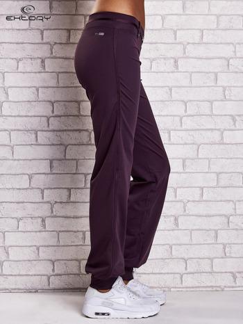 Ciemnofioletowe spodnie dresowe z ozdobnym paskiem                                  zdj.                                  3