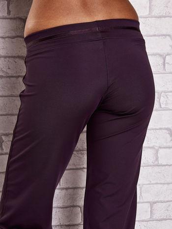 Ciemnofioletowe spodnie dresowe z ozdobnym paskiem                                  zdj.                                  6