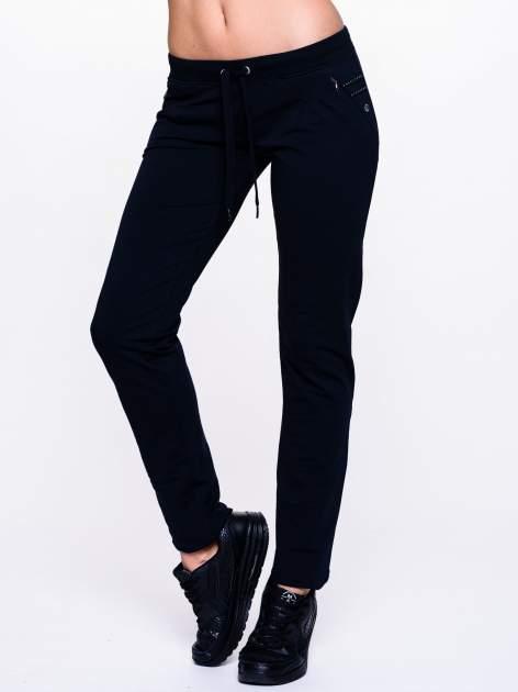 Ciemnogranatowe spodnie dresowe z dżetami przy kieszeniach