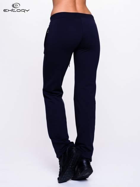 Ciemnogranatowe spodnie dresowe z kwiatem z dżetami i przeszyciem                                  zdj.                                  2