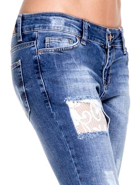 Ciemnoniebieskie spodnie jeansowe z dziurami podszytymi koronką                                  zdj.                                  7
