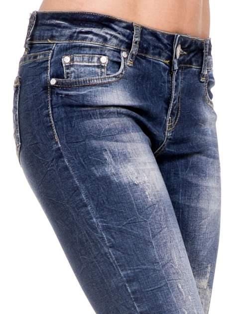 Ciemnoniebieskie spodnie skinny jeans z dziurami i zamkami                              zdj.                              6