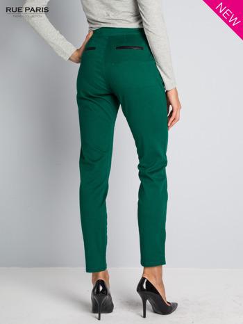 Ciemnozielone spodnie cygaretki ze skórzaną lamówką przy kieszeniach                                  zdj.                                  2