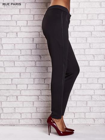 Czarne dopasowane spodnie ze skórzanym prążkiem                                  zdj.                                  3