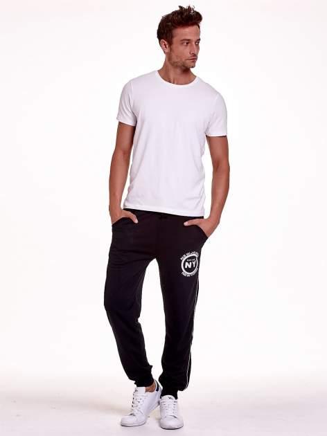 Czarne dresowe spodnie męskie z lampasami po bokach i aplikacją                                  zdj.                                  2