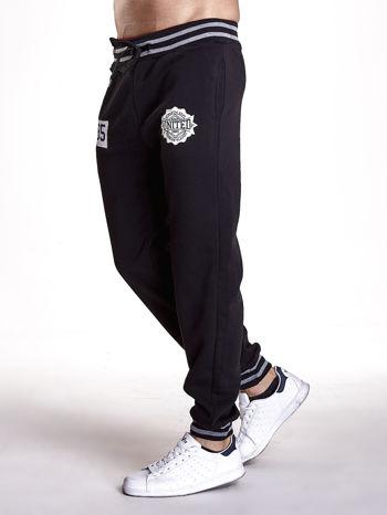 Czarne dresowe spodnie męskie z naszywkami i kieszeniami                                  zdj.                                  2