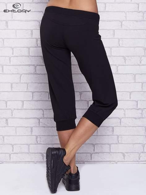 Czarne spodnie capri z troczkami w pasie