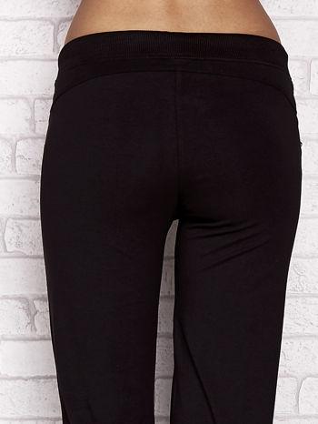 Czarne spodnie dresowe capri z aplikacją na kieszeniach                                  zdj.                                  6