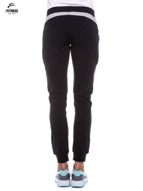 Czarne spodnie dresowe damskie z suwakiem i kontrastowymi wstawkami po bokach                                  zdj.                                  3