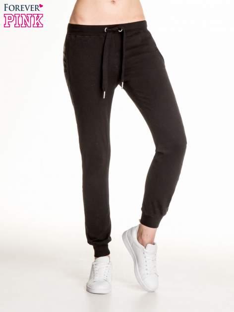 Czarne spodnie dresowe damskie ze skórzanymi lampasami                                  zdj.                                  1